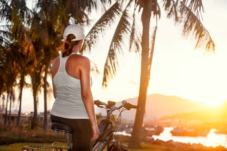 Woman with bicycle on the coast watches a beautiful sunset on a summer day.