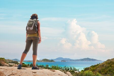 Young woman traveler with backpack looks at beautiful coast with islands during summer holidays in Asia.