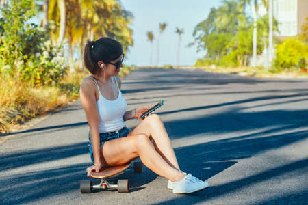 Outdoor summer portrait of resting young woman with longboarding texting her friend Banco de Imagens