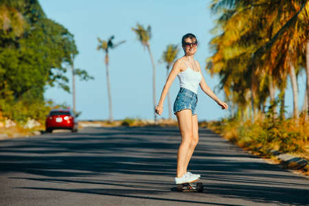 Outdoor summer portrait of cheerful young woman riding longboard in sunny weather Banco de Imagens