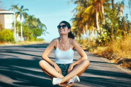 Outdoor summer portrait of a laughing young woman sitting on longboarding after riding Banco de Imagens