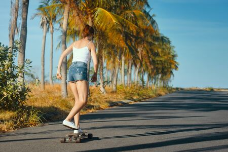 Outdoor summer portrait of cheerful young woman riding longboard in sunny day. View from the back
