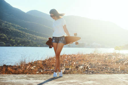 Outdoor summer portrait of young beautiful woman with big longboard desk who have fun alone on sunset background.