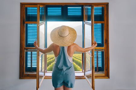 Fashionable woman farmer, dressed in blue jumpsuit shorts, looks out the window with open shutters on grape field on summer sunny day.