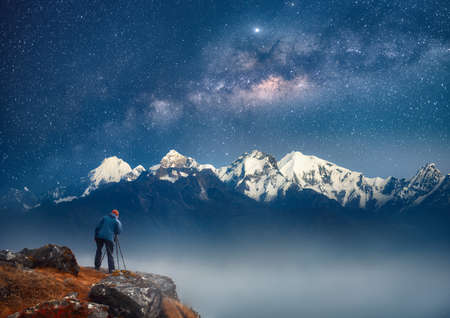 Photographer traveler who take picture of mountains range enjoying stars galaxy of over snowy mountains in the Himalayas, Langtang, Nepal. Night colorful landscape. Scenic sky and mountains at winter in mountains. Banco de Imagens