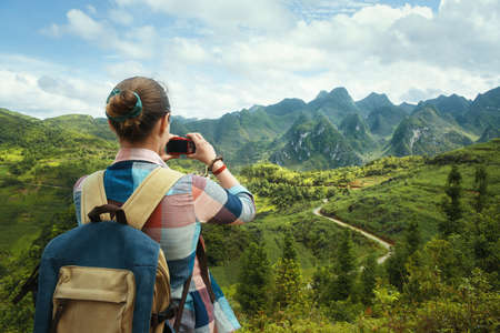 Woman Traveler with backpack, photographs a beautiful view of the karsts mountains in the North of Vietnam. Traveling along mountains, freedom and active lifestyle concept. Banco de Imagens