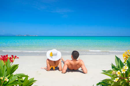 Young couple resting on tropical beach on summer sunny day on background of clear blue sky and turquoise sea.