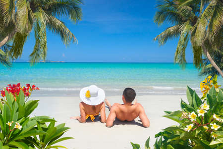 Happy couple resting on a tropical beach on a sunny summer day Banco de Imagens