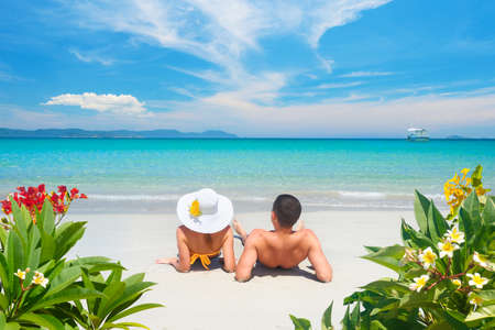 Happy couple resting on tropical beach on summer sunny day on background of beautiful blue sky and turquoise sea.