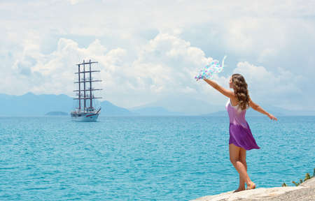 Happy woman in dress waving handkerchief on background of islands and sailing ship on summer sunny day