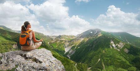 Woman meditating yoga in the mountains sunny Georgia.