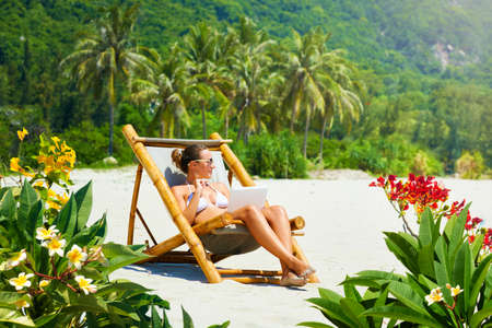 Happy woman with laptop in bamboo chair working remotely on tropical beach