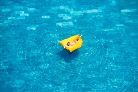 Top view of woman relaxing in swimming pool, tropical vacation holiday concept Banco de Imagens