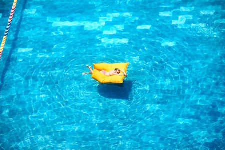 Top view of woman relaxing in an open-air pool. Tropical Summer Vacation Holiday Concept Banco de Imagens