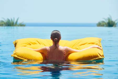Woman relaxes in luxury spa pool near blue ocean. Summer break during summer break.