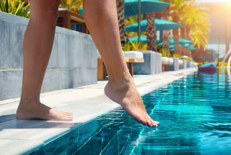 Closeup of female barefoot legs testing swimming pool temperature in sunlight with blur background. Banco de Imagens