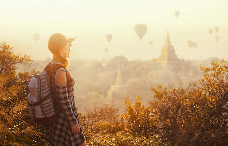 woman traveler with backpack enjoying views of Buddhist stupas and air balloons in ancient Bagan Myanmar