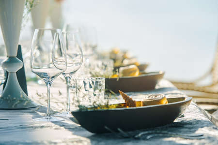 Festive table decor wine glasses and table setting in on beach.. Focus on dish with wineglass