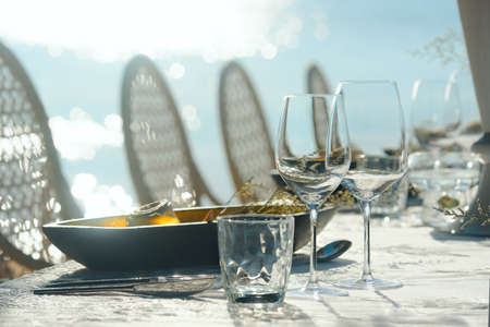 Preparing for an open-air party in beach. Table decor wine glasses and table setting in sunlight.