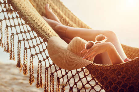 Feet and hand relaxing woman in hammock on the beach during sunset. Banco de Imagens
