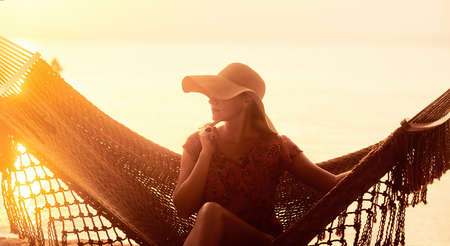 Vacation Beach Summer Holiday Concept. Young pretty woman in hat sitting in hammock at sunset Banco de Imagens