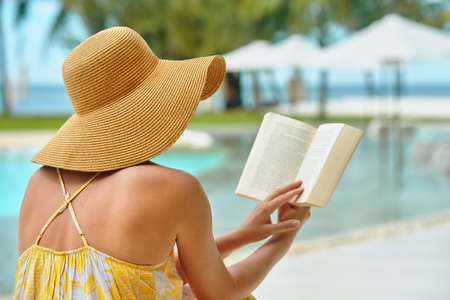 Vacation Beach Summer Holiday Concept. Beautiful woman in hat reading book resting in beach Banco de Imagens