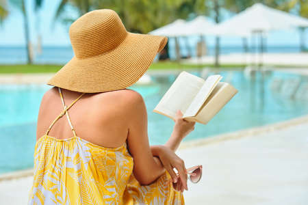 Vacation Beach Summer Holiday Concept. Beautiful woman in yellow dress reading book resting in beach