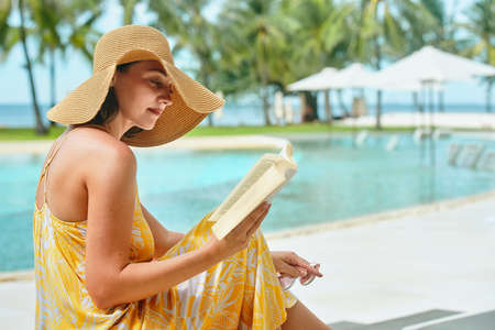 Vacation Beach Summer Holiday Concept. Beautiful woman reading book resting in luxury hotel in summer.