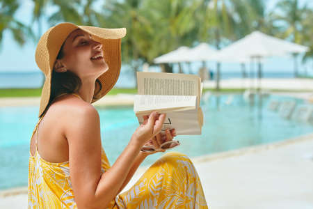 Woman with hat laughs after reading book during summer vacation.
