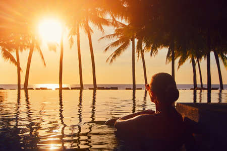 Silhouette woman relaxing in swimming pool on summer beach resort watching sunset. Banco de Imagens