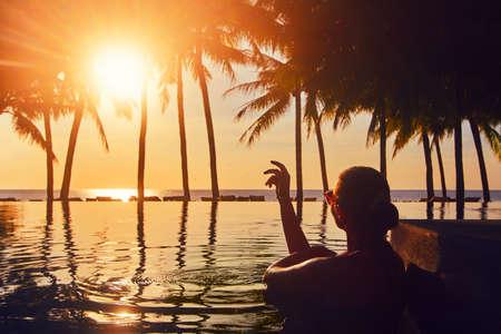 Silhouette woman relaxing in swimming pool on summer beach resort watching sunset. Zdjęcie Seryjne