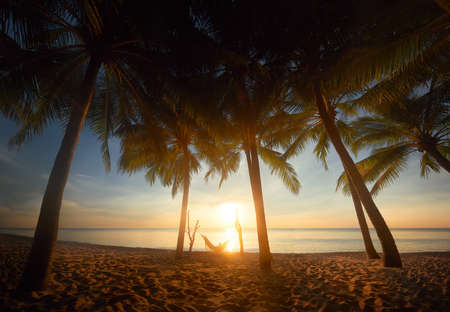 Beautiful sunset over the sea with palmes tree and hammock on the tropical beach in holiday relax time.