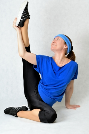 Beautiful athletic girl stretches the muscles photo