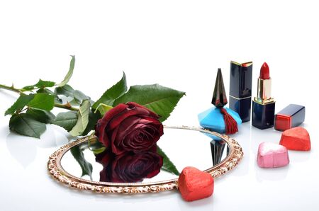 Perfume, lipstick, mirror candy hearts and a red rose in a still life photo
