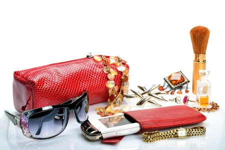 womanish:  Womanish handbag for cosmetics, accessories, mobile phone, brooches, watches, perfumes, sunglasses in still life Stock Photo