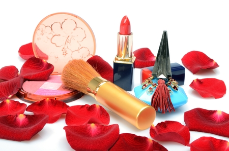Scarlet rose petals and women s decorative cosmetics, perfume in still life photo