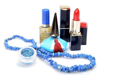 Lipstick, nail polish, perfume and blue necklace in the cosmetic still life photo