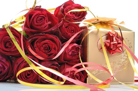 Golden gift box and a bouquet of red roses in a still life photo