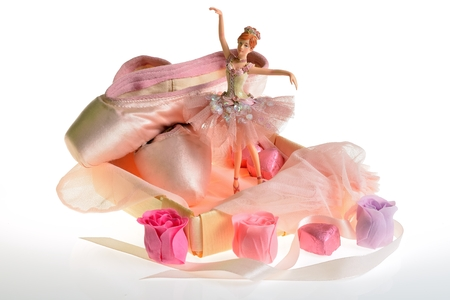 airiness: Pink ballet slippers, pointe shoes and dancing ballerina doll