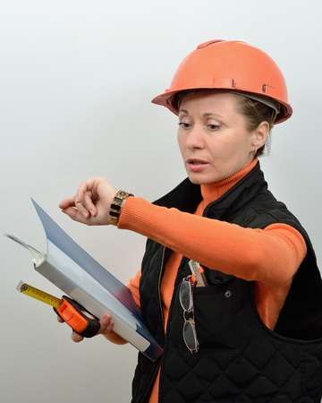 Of construction foreman woman looks at the clock Stock Photo