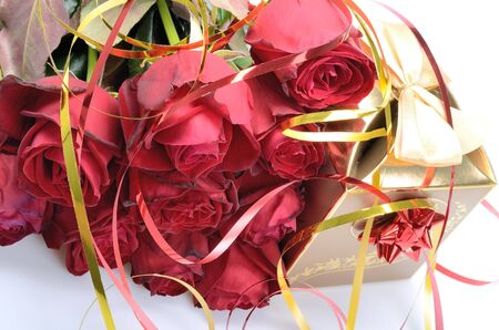 Golden gift box and a bouquet of red roses photo