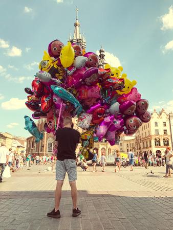 Krakow, Poland - July 29, 2017 : Male street vendor sells colorful popular cartoon character helium balloons