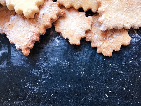 Festive cookies on a black kitchen board with powdered sugar. Restaurant photo with space for your text. View from above