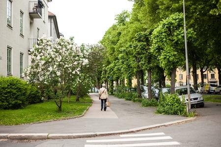 An elderly woman crosses the street in Oslo, Norway
