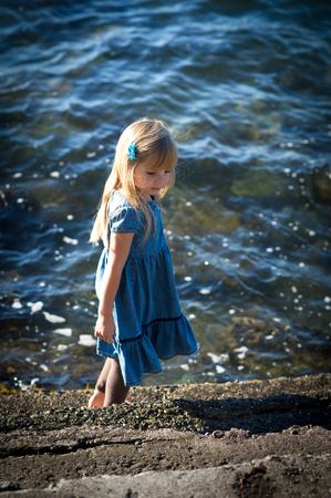 The little girl in a blue dress on the sea.