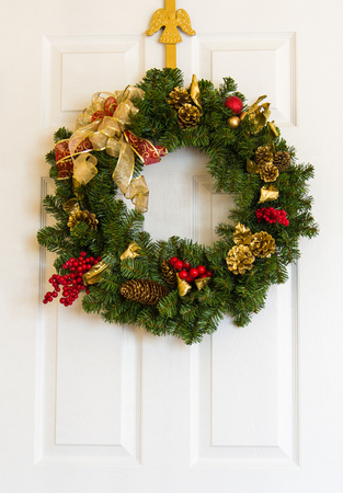 Christmas wreath with red and gold ribbons  on white door.