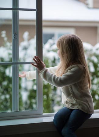 Meisje kijkt uit het raam op een besneeuwde dag. Stockfoto