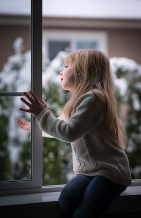 winter window: Little girl looking out the window on a snowy day.