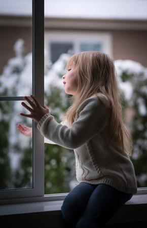 ventana abierta interior: Ni�a mirando por la ventana en un d�a de nieve. Foto de archivo