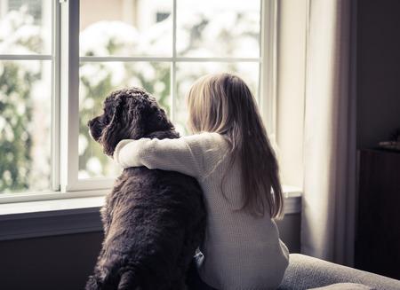 ventana abierta interior: Niña y su perro mirando por la ventana.